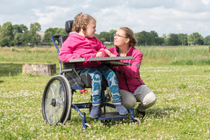 Working with disability / A disabled child in a wheelchair relaxing outside with a special needs carer.
